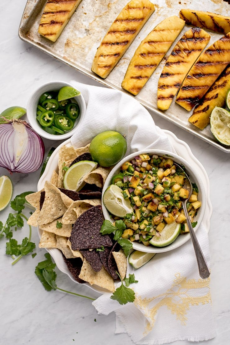 grilled pineapple salsa in a bowl with lime wedges, surrounded by grilled pineapple wedges, jalapeno slices, red onion and cilantro