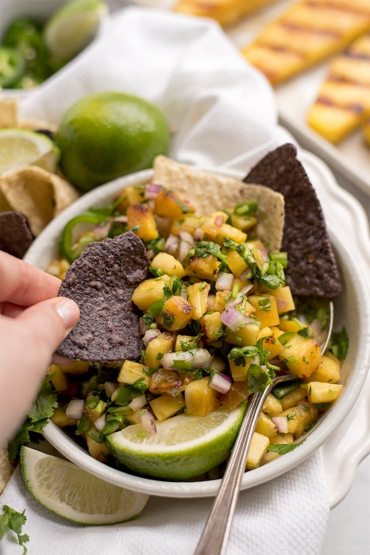 closeup of hand dipping a tortilla chip in a bowl of grilled pineapple salsa