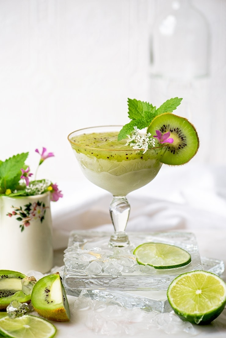 frozen kiwi daiquiri in a stemmed glass with gold rim garnished with kiwi , lemon balm and flowers