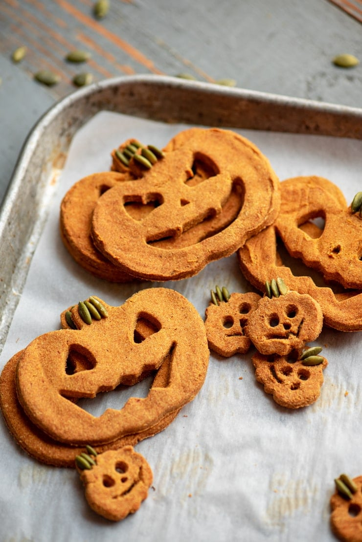 cookie sheet stacked with jack-o-lantern shaped homemade pumpkin dog treats