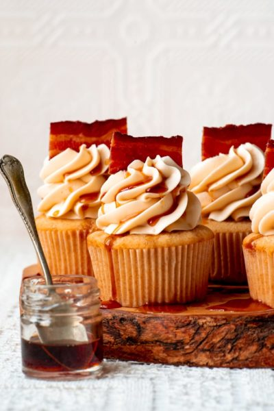 maple bacon cupcakes on a raw edge wooden board