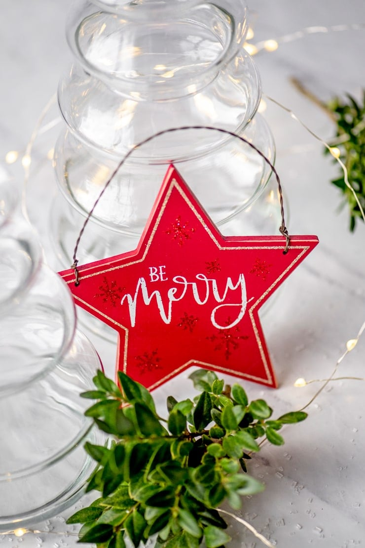 "red star ornament that says ""be merry"""
