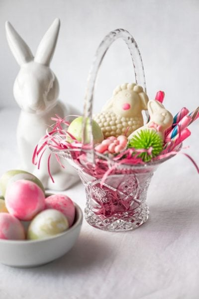 glass easter basket filld with pink grass and white choocolate benny and sheep next to bowl of easter eggs and white ceramic rabbit
