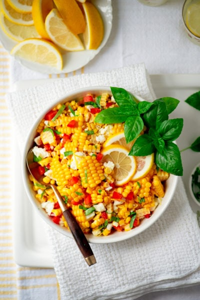 summer corn salad in a bowl with serving spoon and lemon wheels and basil tops for garnish