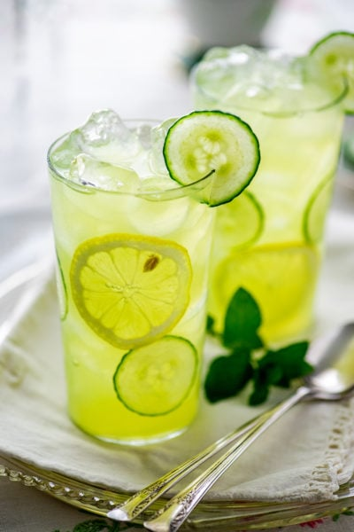 two glasses of cucumber lemonade on a glass tray with iced tea spoons