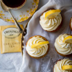 top down photo of cupcakes with piped buttercream and lemon slices next to a Twinings earl grey tea bag and a cup of tea