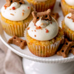 bacon and cheese pupcakes on a white cake pedestal. They are decorated with bacon bits and dog treats