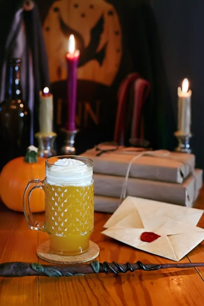 Picture of butterbeer on a wood table with candle burning in the background and a wand in the foreground