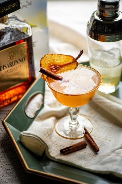 martini garnished with candied pear and cinnamon stick on a green tray lined with a cloth napkin. In the background is a cocktail shaker and a bottle of amaretto
