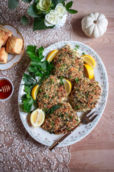 panko crusted turkey cutlets on a platter with parsley, sage and lemon wedges