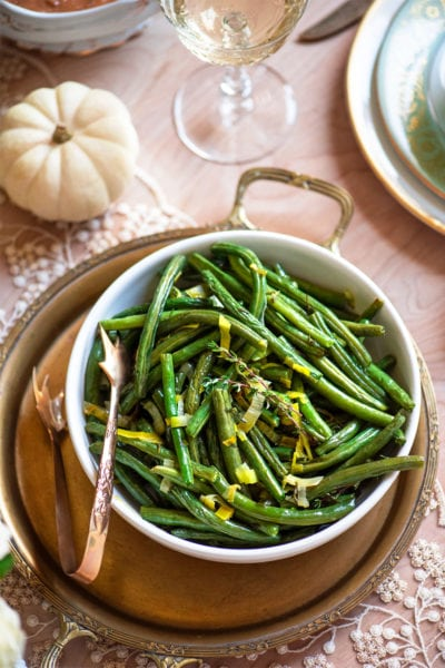 roasted green beans in a white bowl on a brass tray