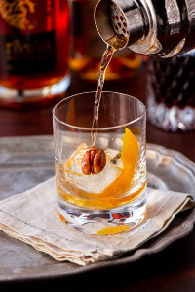 pouring old fashioned into a double rocks glass